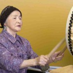 """Woman drumming at Uchida music therapy session, Japan"""